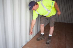 A worker inspecting the flooring of a container
