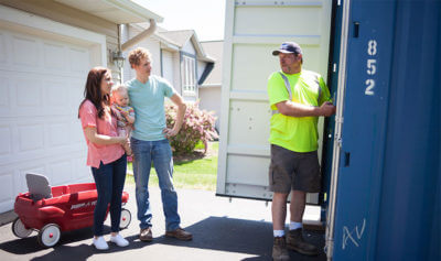 A family standing on their driveway talking to the delivery driver of their new container